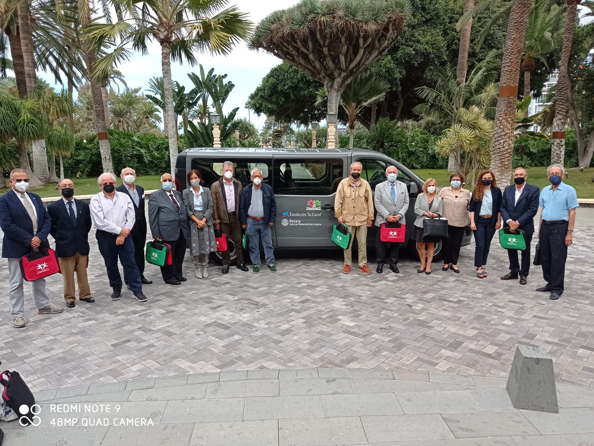 FOTO DE FAMILIA DE UN PEQUEÑO GRUPO DE ROTARIOS ANTE LA FURGONETA DONADA A FUNDACION MAIN EN HOTEL SANTA CATALINA